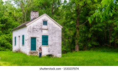 Woman standing by lock keepers white house with green shutters and door on the Chesapeake and Ohio Canal