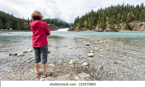 A woman standing by a river watching a waterfall in the Canadian Rocky Mountains.