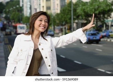 Woman standing by road, waving for taxi