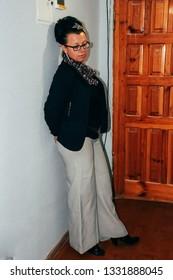 Woman standing in corridor of flat next to door