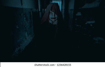 Woman is standing in a darkness dressed in a black hooded cloak in an image of a nun possessed by demons. Cosplay.