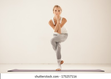 Woman standing in the Eagle yoga pose.