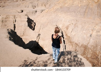 Woman standing at the edge of a precipice. The deep ravines are formed by spring streams that erodes mounds.