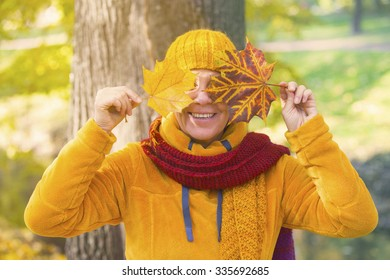 woman standing in the fall in front of tree and holding leaves in front of her eyes