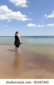 Woman standing with feet in the water watching towards the horizon. Sky is blue with tiny clouds