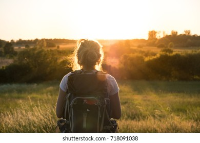 Woman standing in field watching the sunset