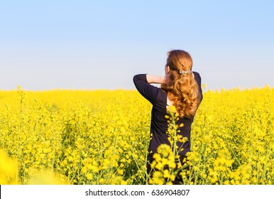 Woman is standing in a field with yellow flowers in the evening.