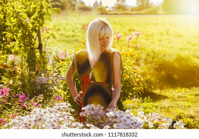 Woman standing at the flower bed in a sunny day