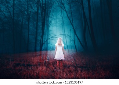 Woman standing in foggy mysterious fantasy forest with grass on the floor. The image with the effect of double exposure.