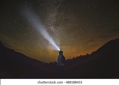 Woman is standing in the forest and pointing the Milky Way ,Carpathian ,Ukraine