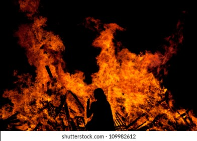 woman standing in front of a big fire