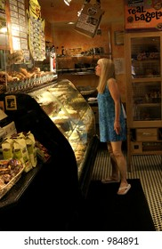 Woman standing in front of dessert counter at Zingerman's Deli in Ann Arbor, Michigan