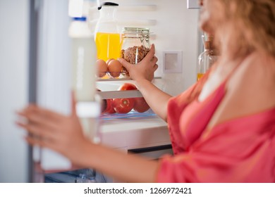 Woman standing in front of fridge full of groceries and looking for something to eat. Picture taken from the inside of fridge.
