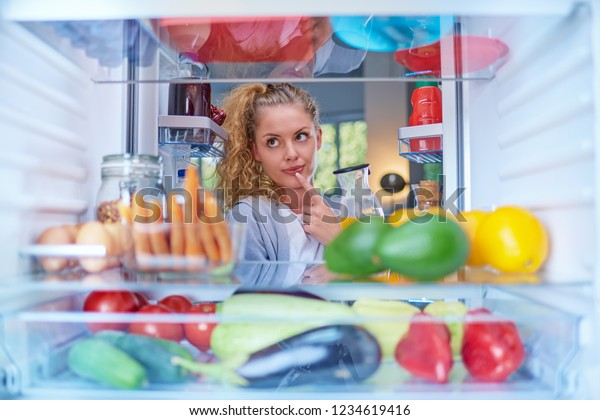 Woman standing in front of fridge full of groceries and taking juice. Picture taken from inside of fridge.