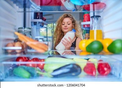 Woman standing in front of fridge and taking milk. Fridge full of groceries.