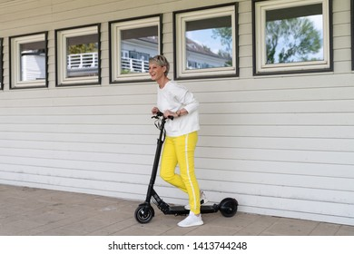 Woman is standing in front of house wall with electric scooter
