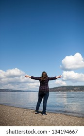 Woman standing in front of the ocean with her arms wide open.