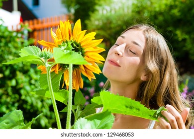 Woman standing in the garden and enjoying the free time