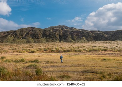 Woman standing in the green lanscape with mountain Aso background, Kusasenri, Aso, Kumamoto, Kyushu, Japan