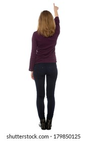 Woman standing with her back to the camera in black tights writing on a virtual screen or pointing upwards, isolated on white
