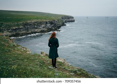 woman standing with her back looking at the sea, beautiful nature, trip, fresh air