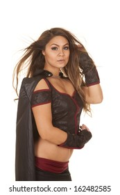 A woman is standing with her hair blowing wearing a bandit costume.