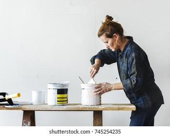 Woman standing holding mix a color in a can