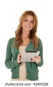 A woman standing and holding on to her tablet with a smile on her face.