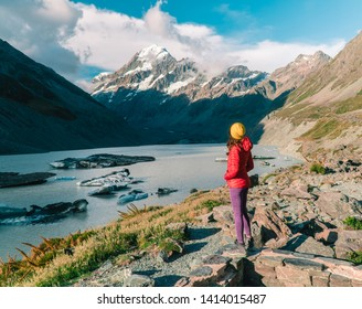 Woman standing at ice Glacier lake at the top of Mount Cook from the Hooker trail tramping trek. Dramatic. Snow capped Mountain background. Grey red moody. Shot in Pukaki South Island, New Zealand.