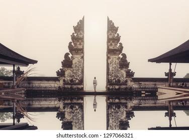 Woman standing in Indonesian temple gate in Lempuyang, Bali