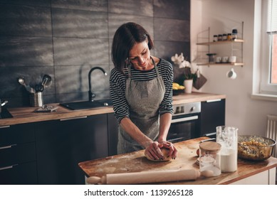 Woman standing in the kitchen by the old wooden table and kneading dough