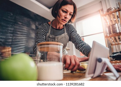 Woman standing in the kitchen by the wooden table and searching apple pie recipe on the tablet