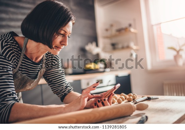 Woman standing in the kitchen by the wooden table and searching apple pie recipe on the smart phone