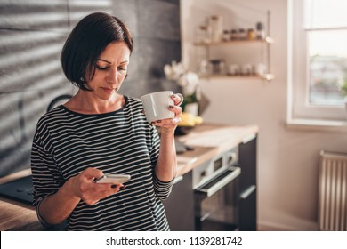 Woman standing in the kitchen drinking coffee and using smart phone