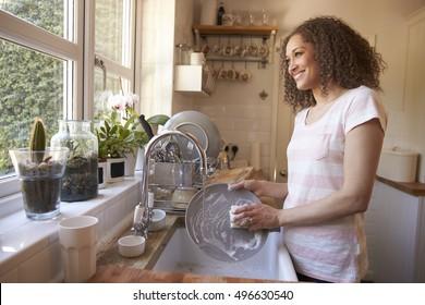 Woman Standing At Kitchen Sink Washing Up