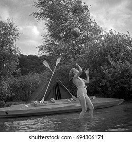 Woman standing in lake and catching ball