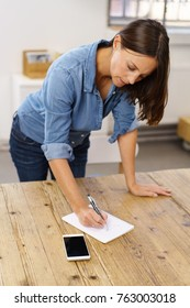 Woman standing at a large wooden table writing notes on a notepad with a serious expression of concentration