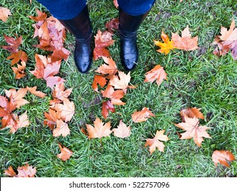 Woman standing in leaves on grass on rainy day.