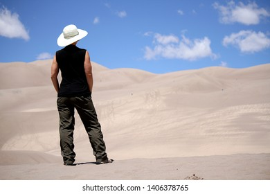 A woman standing looking into the Great Sand Dunes National Park, Colorado.