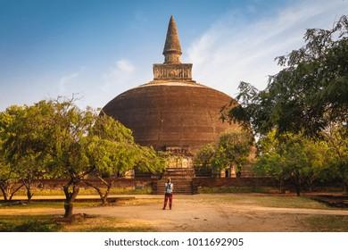 Woman standing and looking on stupa Rankot Vihara, Unesco ancient city of Polonnaruwa, Sri Lanka