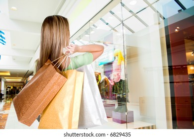 woman standing in mall with shopping bags