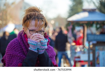 A woman is standing in a market in the winter drinking a cup of tea