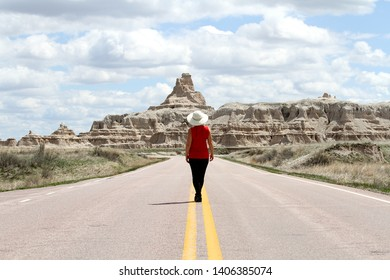 A woman standing in the middle of the road in the Badlands National Park in South Dakota.