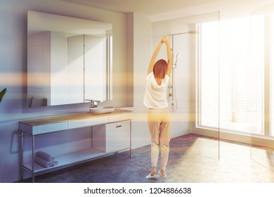 Woman standing in modern bathroom corner with white walls, concrete floor, sink standing on white countertop and large mirror. Glass door shower. Toned image