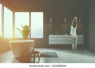 Woman standing in modern bathroom interior with gray walls, concrete floor, window with gray curtains, white bathtub and double sink. Toned image double exposure