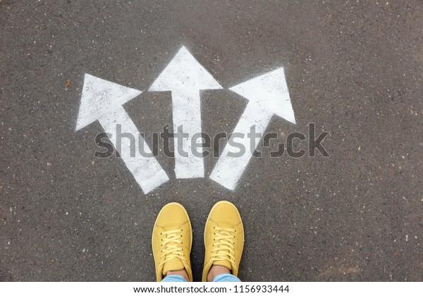 Woman standing near arrows on asphalt, top view. Choice concept