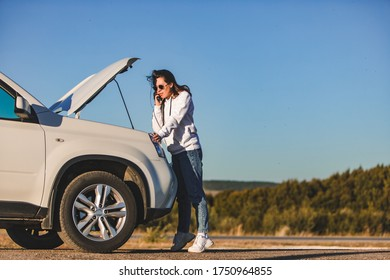 woman standing near car with opened hood on sunset talking on phone