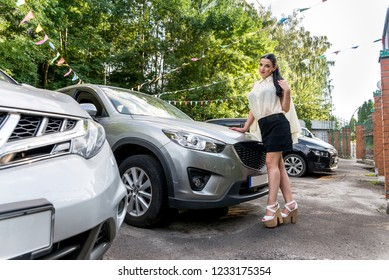 Woman standing near car and posing for camera