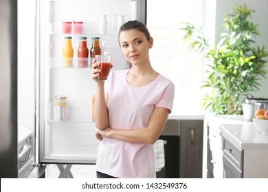 Woman standing near open fridge at home