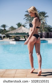 woman standing near swimming pool in a black bathing suit, perfect figure, summer sun sea